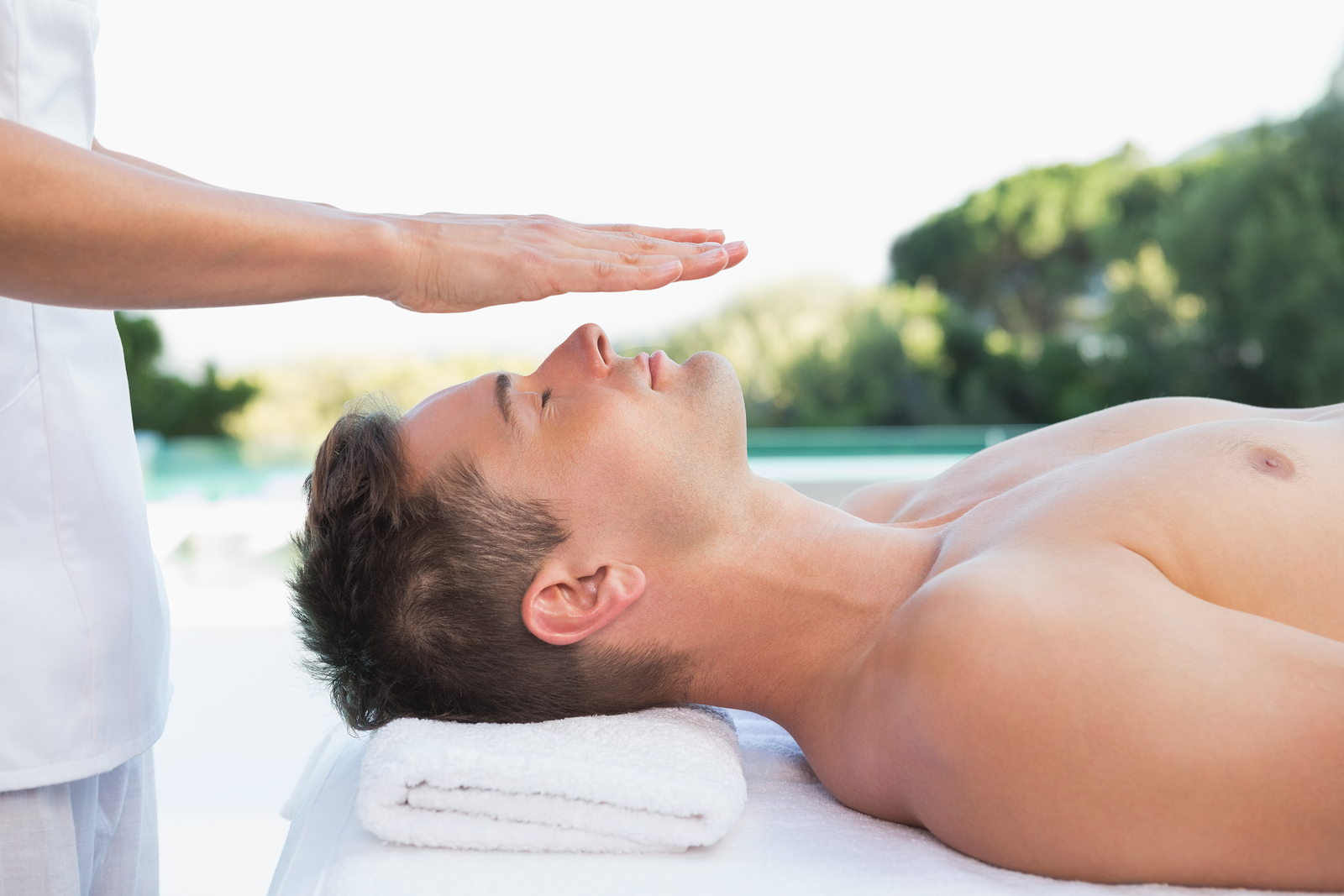 Peaceful man getting reiki treatment poolside outside at the spa